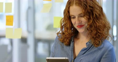 клейкий : Businesswoman reading sticky notes and digital tablet in the office 4k