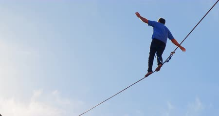 tightrope : Low angle view of highline athlete walking on slackline 4k