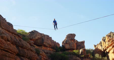 slacklining : Low angle view of man falling from slackline in rocky mountains 4k
