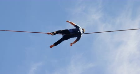 slacklining : Low angle view of man relaxing on tight rope 4k