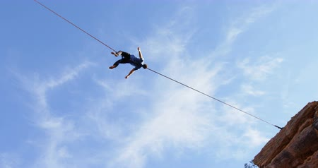 tightrope : Low angle view of man relaxing on tight rope 4k