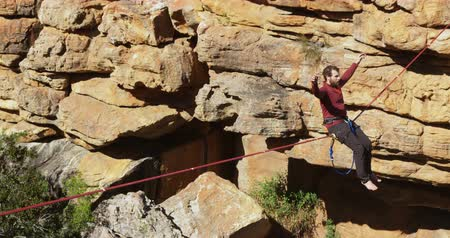 slacklining : Man relaxing on tight rope in rocky mountain 4k