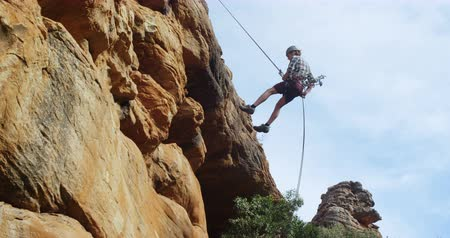 tightrope : Mountaineer rappelling down the cliff with the help of rope on a sunny day 4k