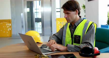 earmuffs : Male worker using laptop and digital tablet at desk in office 4k Stock Footage