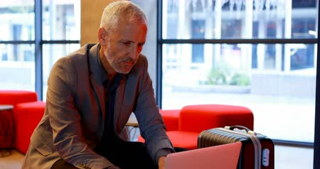sofistike : Mature businessman using laptop in hotel lobby 4k