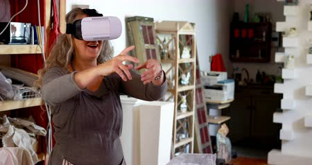 oleiro : Mature female potter using virtual reality headset in pottery shop 4k