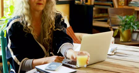 diary : Mature woman having juice while using laptop at home 4k