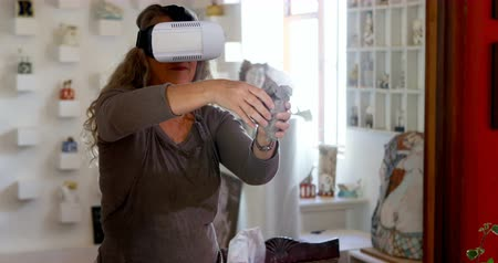 shaping : Mature female potter molding a clay while using virtual reality headset in pottery shop 4k
