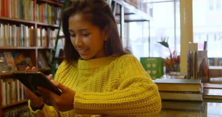 adolescência : Smiling teenage girl using digital tablet in library 4k