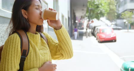 svetr : Teenage girl drinking coffee on sidewalk on a sunny day 4k