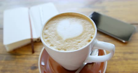 absence : Cup of hot coffee latte with heart shaped foam art with diary and mobile phone on table 4k