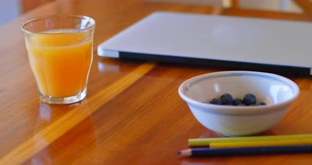 absence : Orange juice with laptop, blueberries and colored pencil on a table at home 4k