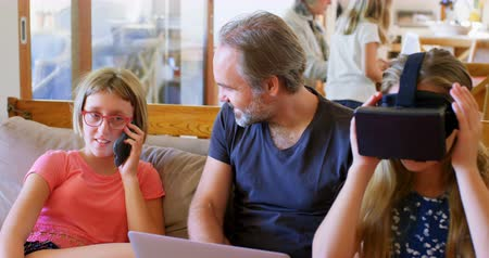 livingroom : Father using laptop while daughter talking on mobile phone living room at home 4k