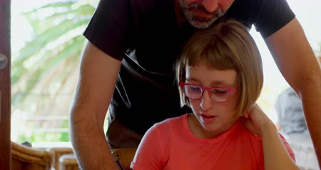 homely : Father helping daughter in her homework at home 4k Stock Footage