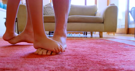 yalınayak : Father and daughter dancing together in living room at home 4k Stok Video