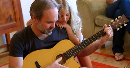 fondness : Father playing guitar with her daughter in living room at home 4k Stock Footage