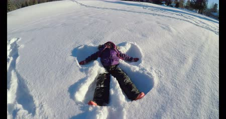 рекреационных преследования : Kid making snow angels in snow during winter on a sunny day 4k