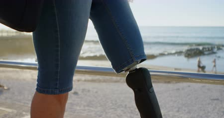 amputee : Disabled woman using mobile phone while walking in the beach on a sunny day 4k
