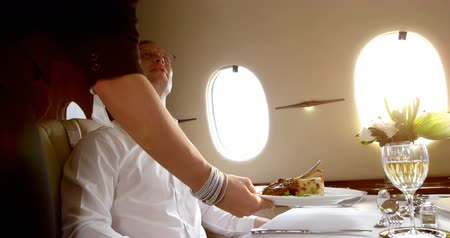 lavish : Flight attendant serving meal to businessmqn in private jet 4k Stock Footage