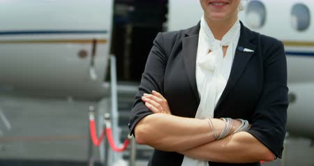 lavish : Portrait of flight attendant standing with arms crossed on a runway 4k Stock Footage