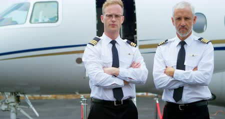 pilots : Portrait of two male pilots standing with arms crossed on a runway 4k