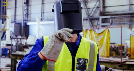 welding helmet : Portrait of male engineer holding welding torch in workshop 4k