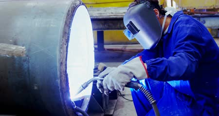 welding helmet : Male engineer using welding torch in workshop 4k Stock Footage