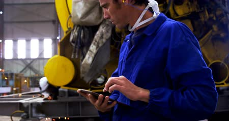 marine technology : Male engineer using digital tablet in workshop 4k
