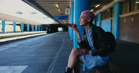 платформа : Pink hair woman talking on mobile phone in railway station 4k