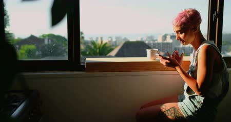 pronikavý : Pink hair woman sitting near window and using mobile phone 4k Dostupné videozáznamy