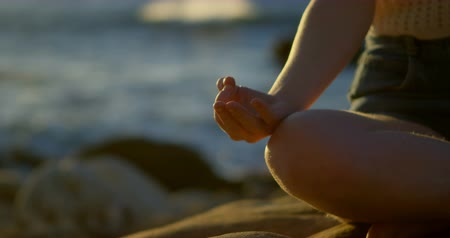 meditando : Yong woman performing yoga on the beach 4k