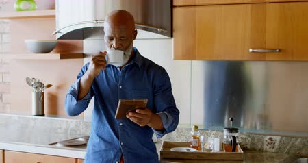 emeryt : Senior man using digital tablet while having black coffee in kitchen at home 4k Wideo