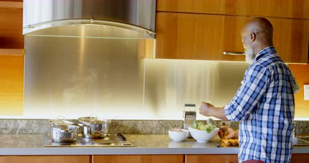 tongs : Senior man preparing vegetable in kitchen at home 4k Stock Footage