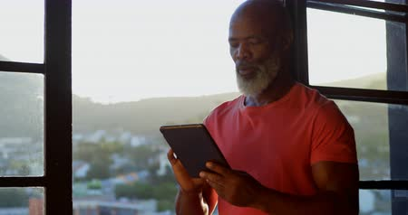 homely : Active senior man using digital tablet at home 4k Stock Footage