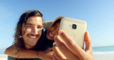 omzunda : Couple taking selfie with mobile phone on the beach 4k