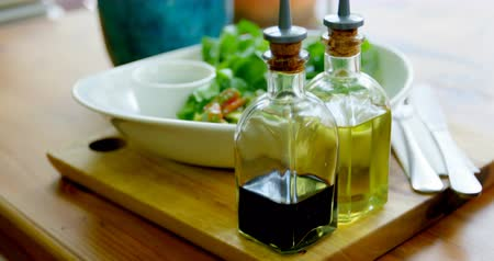 virgem : Close-up of bowl of salad and olive oil bottles on the table in restaurant 4k