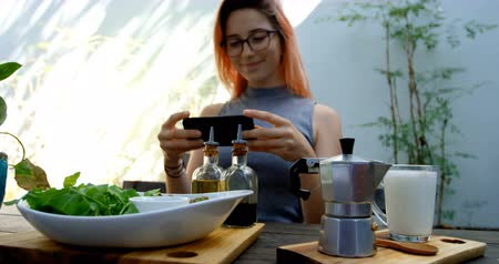 servido : Beautiful young woman photographing salad on the table in restaurant 4k