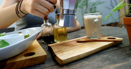 olive oil pour : Young woman preparing coffee on the table in restaurant 4k