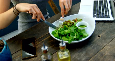 virgem : Young woman having salad on the table in restaurant 4k