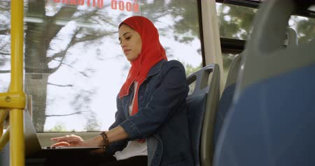busz : Woman in hijab using laptop in the bus 4k