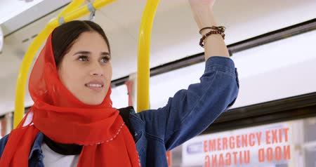 megragad : Close up of woman in hijab standing while travelling in the bus 4k