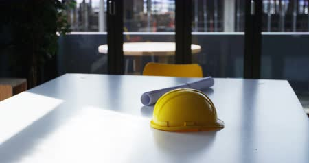 absence : Blueprint and hardhat on a table in office 4k