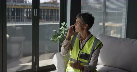 global iş : Female engineer talking on mobile phone in office 4k
