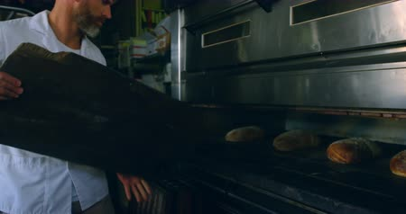 pékség : Male chef removing bread from oven in kitchen 4k