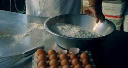 гостеприимство : Close up of male Chef mixing egg and flour in kitchen 4k