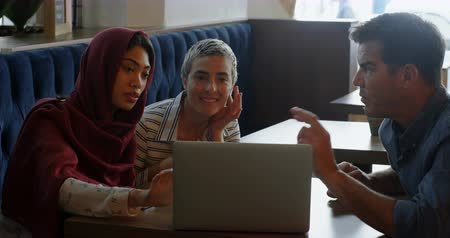 kafeterya : Friends discussing over laptop on table at cafe 4k