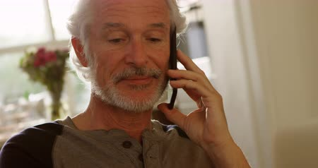 valódi : Close-up of senior man talking on mobile phone at home 4k Stock mozgókép
