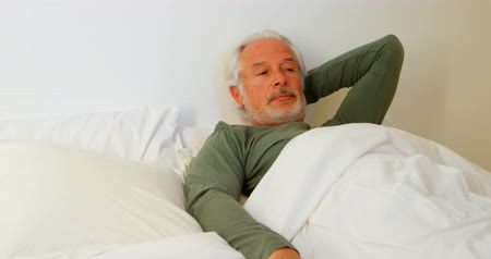 ev hayatı : Senior man relaxing on bed in bedroom at home 4k
