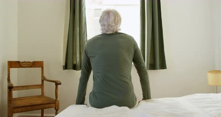 domácké : Rear view of senior man sitting on bed in bedroom at home 4k