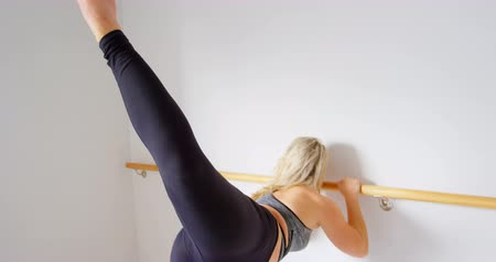 rugalmas : Beautiful woman stretching at barre in fitness studio 4k Stock mozgókép